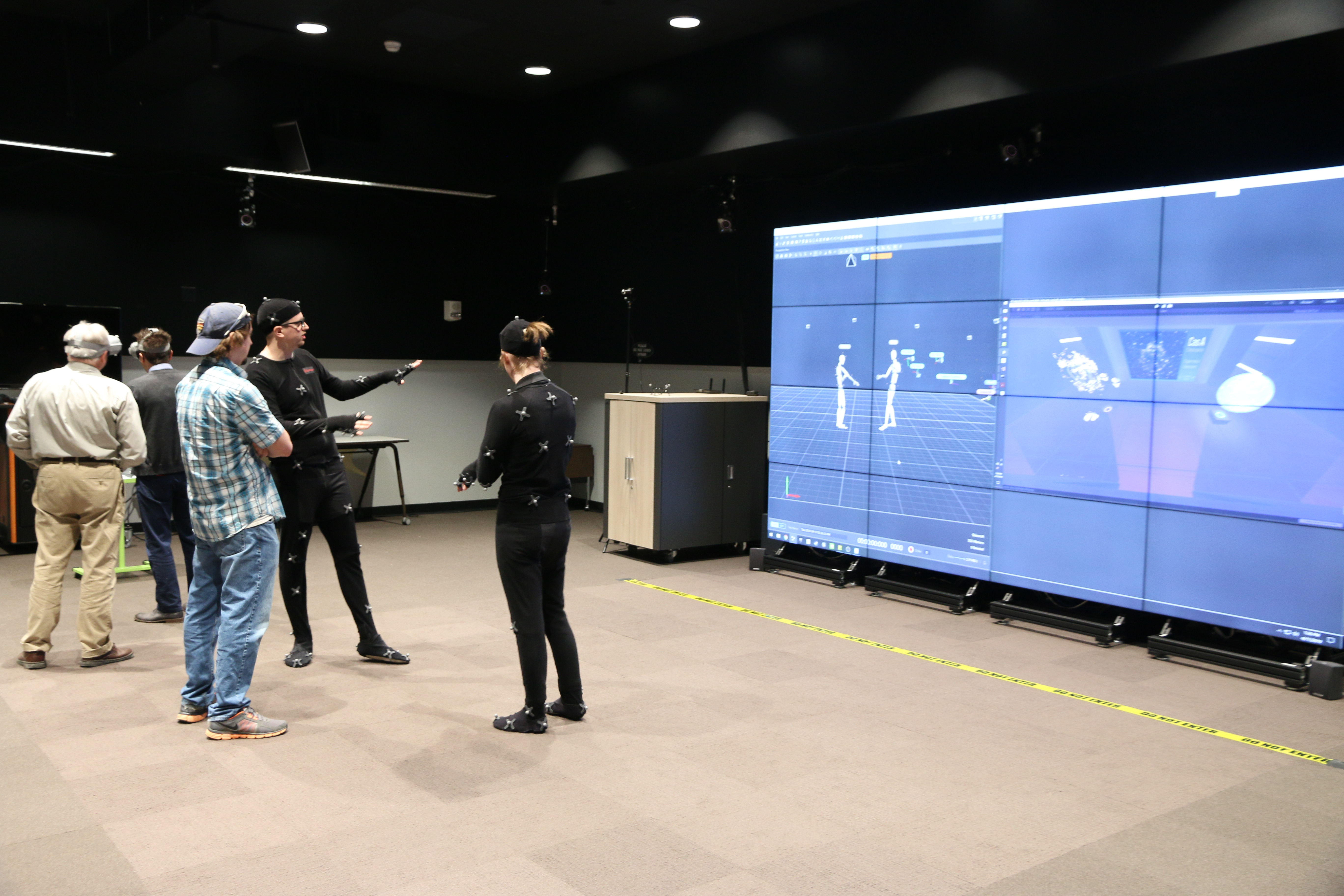 Envision Center students demonstrating the motion capture suits that track a user's movement and insert a representation of the user into the virtual environment